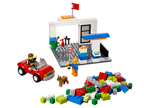 Keep the sports car on the road with the LEGO<sup>®</sup>Juniors Vehicle Suitcase with gas station, 2 minifigures, dog and lots of LEGO bricks.
