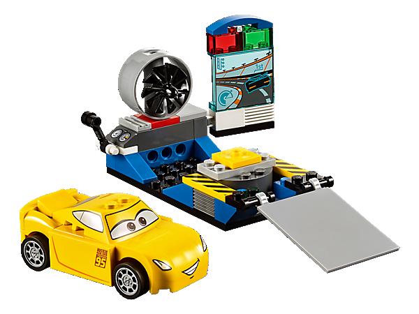 Hilf Disney•Pixars Cruz Ramirez beim Training im Rennsimulator. Der Rennsimulator enthält ein drehbares Gebläse, einen Bildschirm, eine Rampe sowie einen einfach zu bauenden LEGO® Juniors Charakter.