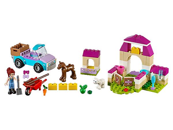 Les animaux se transportent vers la ferme, comprenant une camionnette, une étable, un enclos, et des accessoires de ferme, une valisette LEGO Juniors facile à transporter, une minipoupée de Mia et des figurines de poulain et d'agneau.