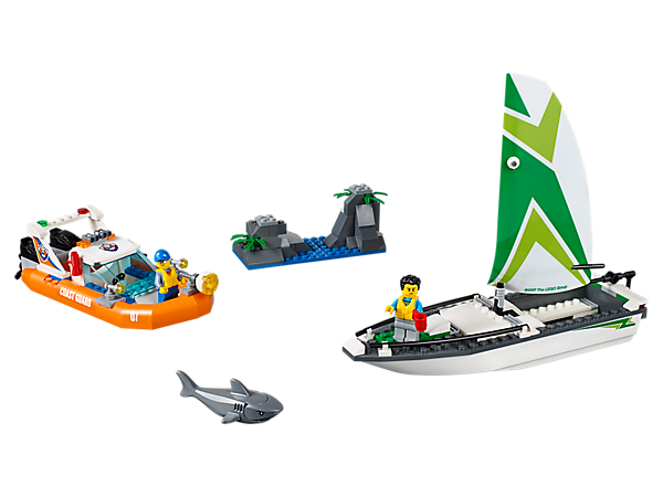 Pull off a daring sailboat rescue with the LEGO® City coast guard, featuring a rescue craft, sailboat with toppling mast, rock island build, 2 minifigures and a shark figure.